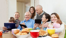 Happy family or friends with electronic devices Royalty Free Stock Photo