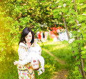 Happy family, friends forever concept. Smiling mother and little son playing together in a park. Mum holding laughing Royalty Free Stock Images