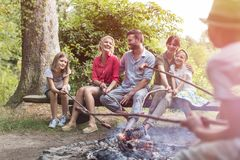 Happy family and friends roasting sausages over burning campfire at park stock photos