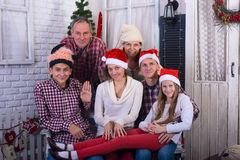 Happy family with friends, in Santa hats royalty free stock photos
