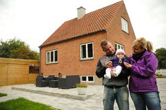 Happy family in front of house Stock Photo