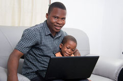 Happy family in front of a laptop. The child is concentrated on the laptop while his father watched the camera Royalty Free Stock Photos