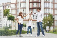 Happy family in front of new apartment building. Adorable little girl reaching to the keys her parents are holding. Family posing outdoors in front of a modern Royalty Free Stock Photography