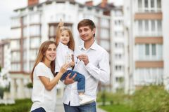 Happy family in front of new apartment building. Cute little girl smiling showing thumbs up her parents holding keys to their new home in apartment building on Stock Image