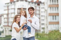 Happy family in front of new apartment building. Cute little girl smiling showing thumbs up her parents holding keys to their new home in apartment building on Royalty Free Stock Images