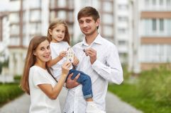 Happy family in front of new apartment building. Lovely young family holding keys to their new apartment smiling joyfully posing outdoors. Husband and wife with Stock Images