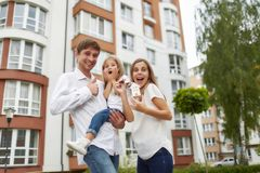 Happy family in front of new apartment building. Young family looking excited moving into their new home screaming joyfully holding keys to their apartment Stock Photo