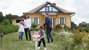 Happy family in front of their new house.  stock footage