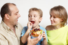 Happy family with fruit salad royalty free stock photography