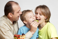 Happy family with fruit salad royalty free stock photos