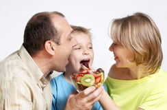 Happy family with fruit salad stock images