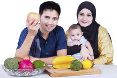 Happy family with fruits on the table Stock Photos