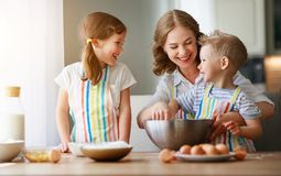 Happy family funny kids bake cookies in kitchen. Happy family  funny kids are preparing the dough, bake cookies in the kitchen stock photography