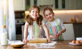 Happy family funny kids bake cookies in kitchen. Happy family  funny kids are preparing the dough, bake cookies in the kitchen royalty free stock photos