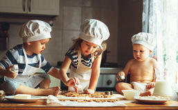 Happy family funny kids bake cookies in kitchen Stock Photography