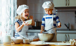 Happy family funny kids bake cookies in kitchen. Happy family funny kids are preparing the dough, bake cookies in the kitchen royalty free stock images