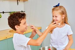 Happy family funny kids are preparing the dough, playing with flour in the kitchen. Funny kids in white t-shirts stain their face with white flour royalty free stock image