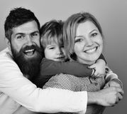 Happy family game. Mother, father and son with smiling faces hug on blue. Background. Man with beard, women and son happy together. Joyful family and stock photo