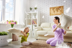 Happy family games. Happy family! The mother and her child girl are fighting pillows. Happy family games Stock Image
