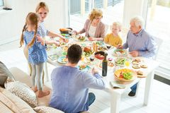Happy Family Gathering in Sunlight. High angle portrait of happy two generation family enjoying dinner together sitting at festive table with delicious dishes stock photo