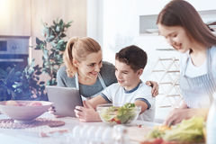 Happy family gathering together in kitchen. Children are precious. Selective focus on a beaming mother embracing her little son while he sitting at a kitchen Stock Photos
