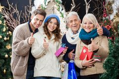 Happy Family Gesturing Thumbs Up In Christmas. Portrait of happy family with Christmas presents and shopping bags gesturing thumbs up in store Royalty Free Stock Image