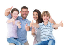 Happy family gesturing thumbs up. Portrait of happy family gesturing thumbs up over white background stock images