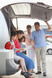 Happy family getting ready for a trip, looking at map by the car Stock Image