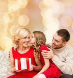 Happy family with gift box. Christmas, holidays, family and people concept - happy mother, father and little girl with gift box kissing over beige lights Royalty Free Stock Image