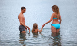 Happy family with girl bathe in sea, standing back Stock Photo