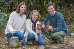 Happy Family Girl Child Father Mother Daughter Gardening. Attractive, successful and happy family, man, woman, girl child, mother, father and daughter gardening Stock Photography