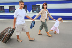 Happy family with girl going on railway station Stock Photography