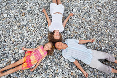 Happy family with girl lying on beach, closed eyes Stock Photos