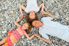 Happy family with girl lying on beach, closed eyes stock images