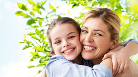 Happy family of girl and mother hugging Stock Photography