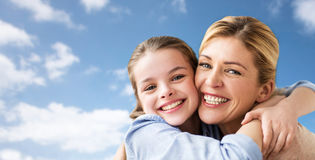 Happy family of girl and mother hugging over sky. Mothers day, people and family concept - happy smiling girl with mother hugging over blue sky and clouds Stock Images