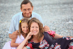 Happy family with girl sitting on beach Royalty Free Stock Photos