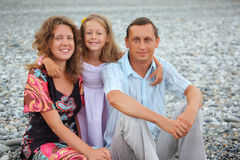Happy family with girl sitting on stony beach Stock Images