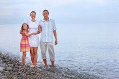Happy family with girl standing on beach Royalty Free Stock Image