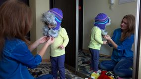 Happy family girls measuring warm winter hats near mirror stock video