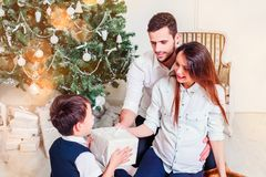 Happy family give gifts in the living room, behind the decorated Christmas tree, the light give a cozy atmosphere. New Year and xmas theme royalty free stock photo