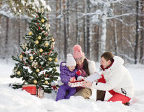 The happy family gives gifts in winter forest Stock Photos