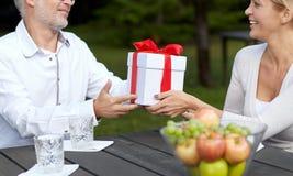 Happy family giving present in summer garden Stock Images