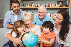 Happy family with globe while sitting on sofa Royalty Free Stock Images