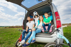 Happy family going for a car trip in summer. Happy family, young parents and two kid boys, sitting in the luggage boot, going for a car trip in summer Stock Photography