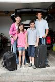 Happy family going on holiday. Standing by their car boot with their luggage Stock Images