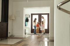 Happy family going out together, parents leaving home with kids. Happy family going out standing in hallway opening door, parents leaving home with kids holding Royalty Free Stock Photography