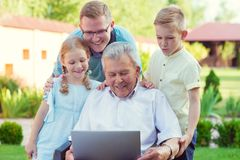 Happy family with grandfather during internet talking on laptop Stock Images