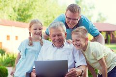 Happy family with grandfather during internet talking on laptop Royalty Free Stock Photography