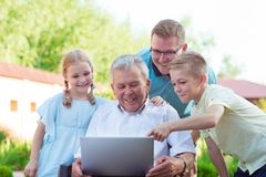 Happy family with grandfather during internet talking on laptop Royalty Free Stock Images